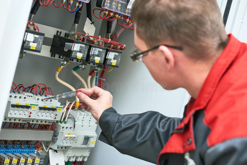 Electricista que examina voltaje actual con el probador del destornillador fotos de archivo libres de regalías