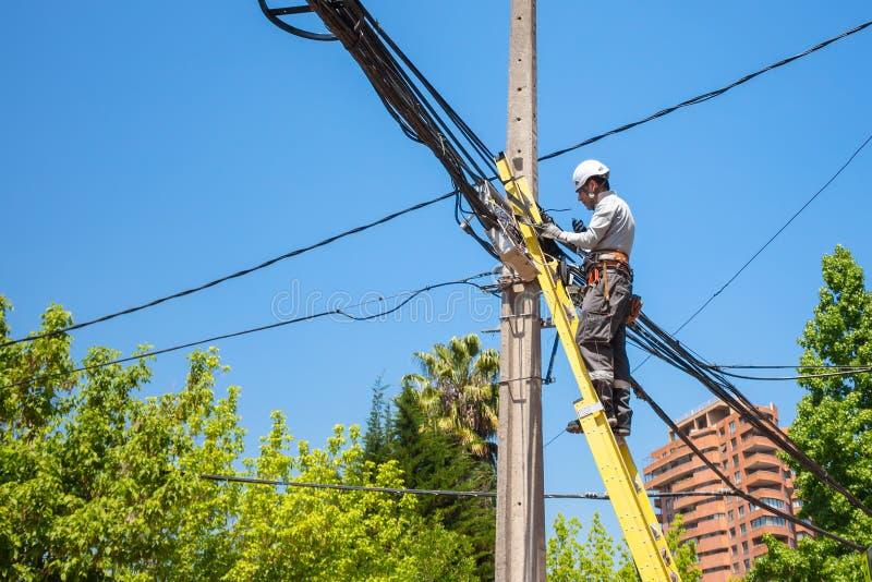 Electricista que fija los cables en el polo de la red de la ciudad adentro imagenes de archivo
