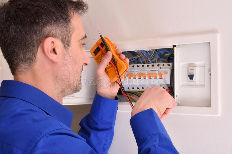 Electricista que hace reparaciones en caja de vivienda eléctrica foto de archivo libre de regalías