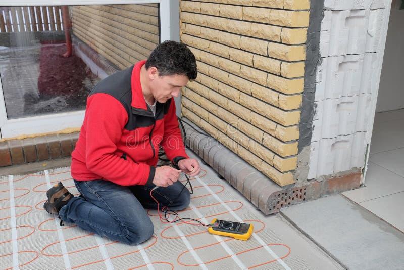 Electricista que instala el cable eléctrico de calefacción en piso concreto Resistencia de la medida del hombre del cable imágenes de archivo libres de regalías