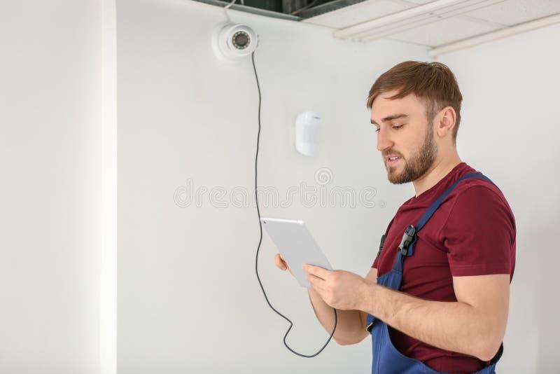 Electricista que instala la cámara de seguridad dentro fotos de archivo libres de regalías