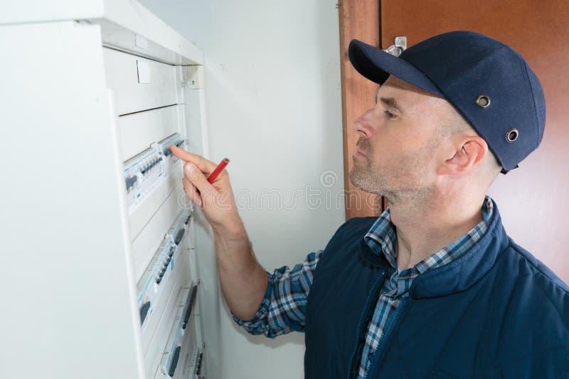 Electricista que mira el fusebox fotografía de archivo libre de regalías