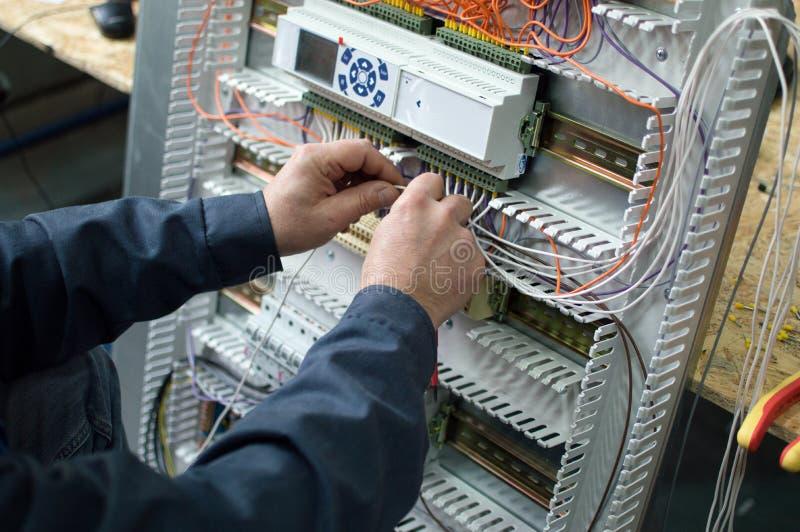 Electricista que monta el cubículo de control industrial de la HVAC en taller Foto del primer de las manos imagen de archivo