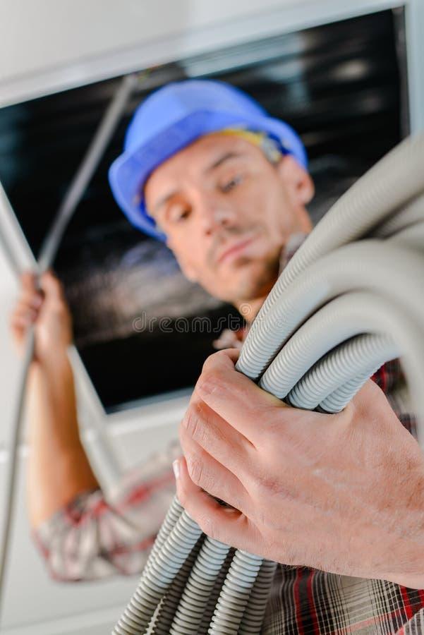 Electricista que repara el cable del techo imágenes de archivo libres de regalías