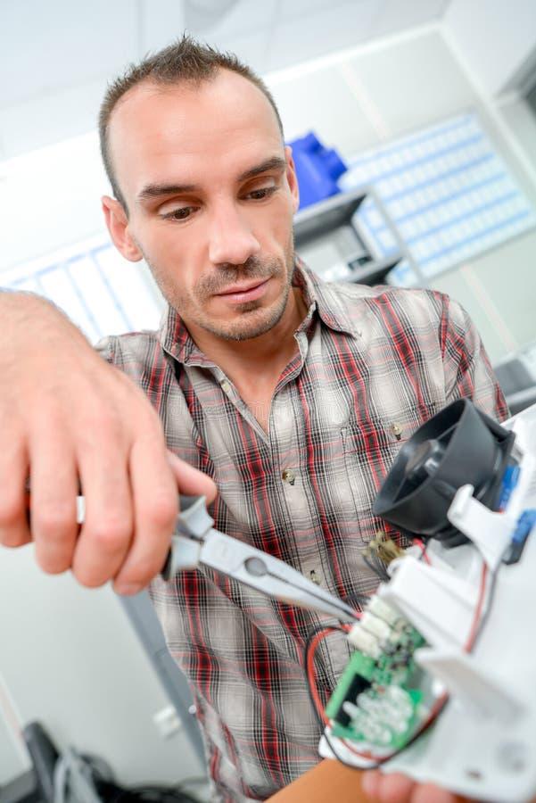 Electricista que repara el dispositivo roto fotos de archivo libres de regalías