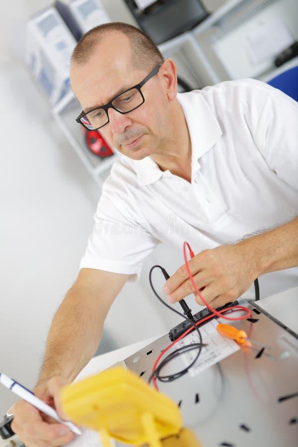 Electricista que repara un dispositivo fotos de archivo libres de regalías