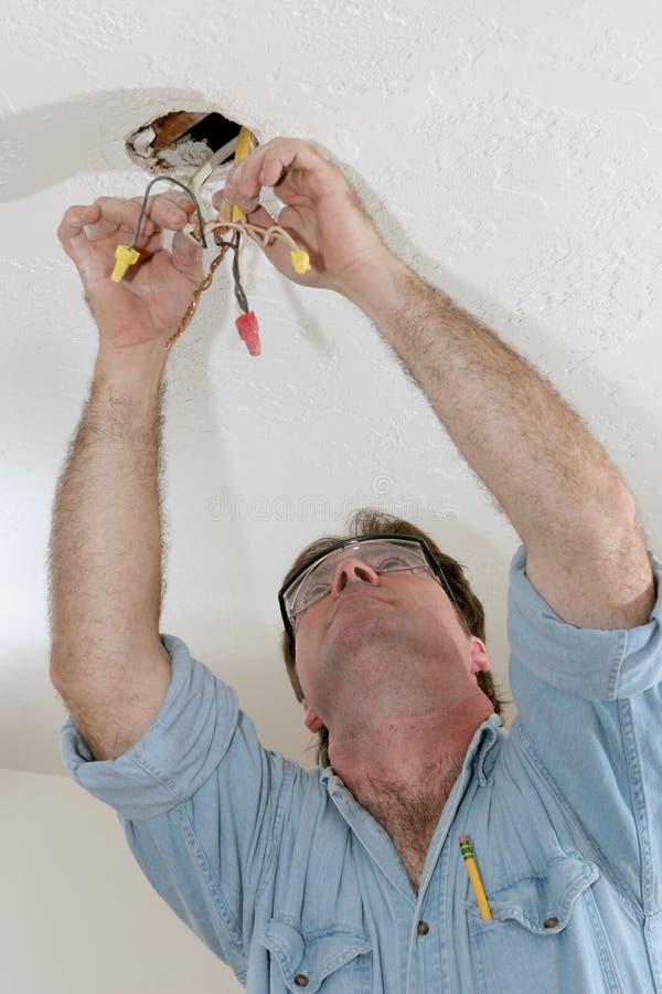 Electricista que tira del alambre imagenes de archivo
