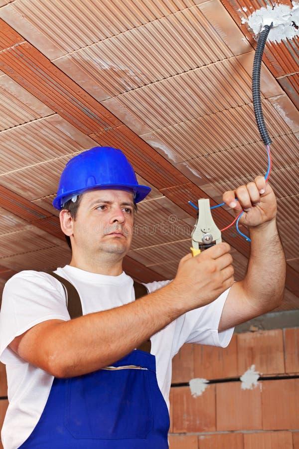 Electricista que trabaja con el cableado en un nuevo edificio imagenes de archivo