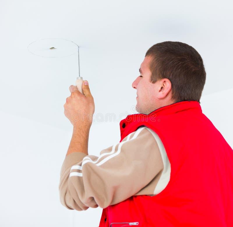 Electricista que trabaja con los alambres y otros utensilios imagen de archivo libre de regalías