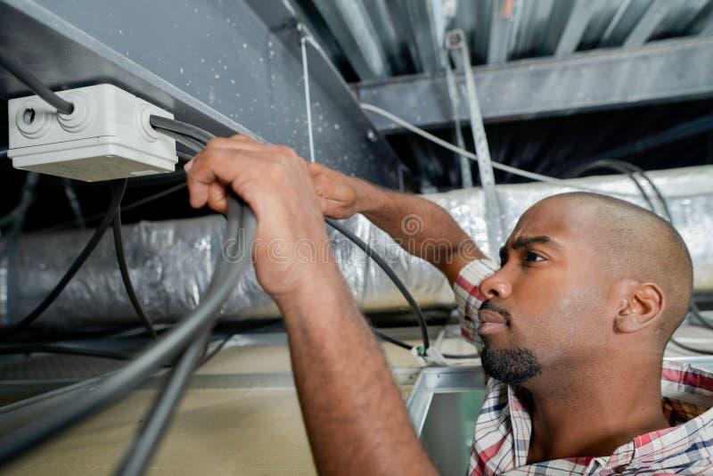 Electricista que trabaja en el cableado del techo fotos de archivo