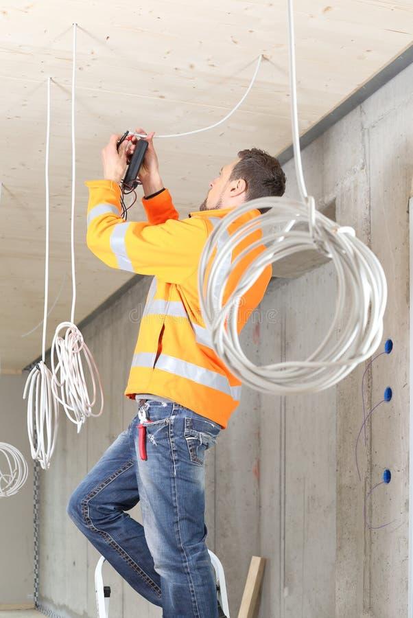 Electricista que trabaja en el nuevo edificio con los cables imagen de archivo