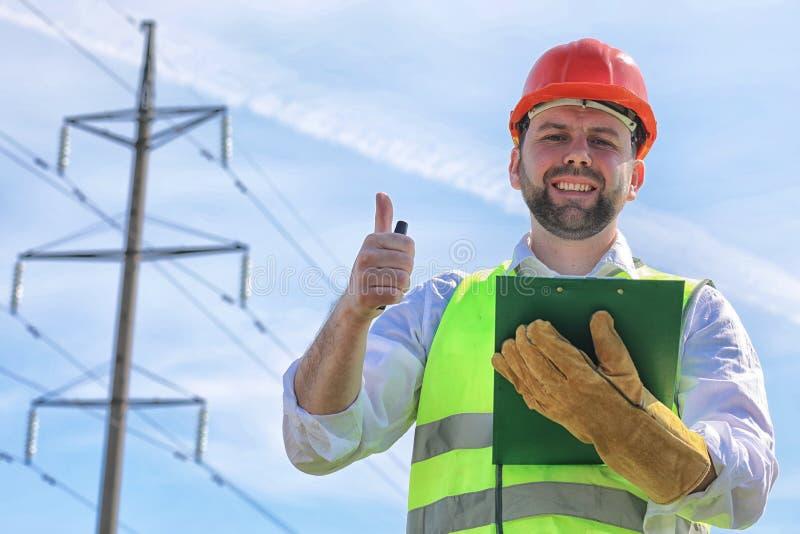 Electricista que trabaja en guantes que llevan de un casco foto de archivo