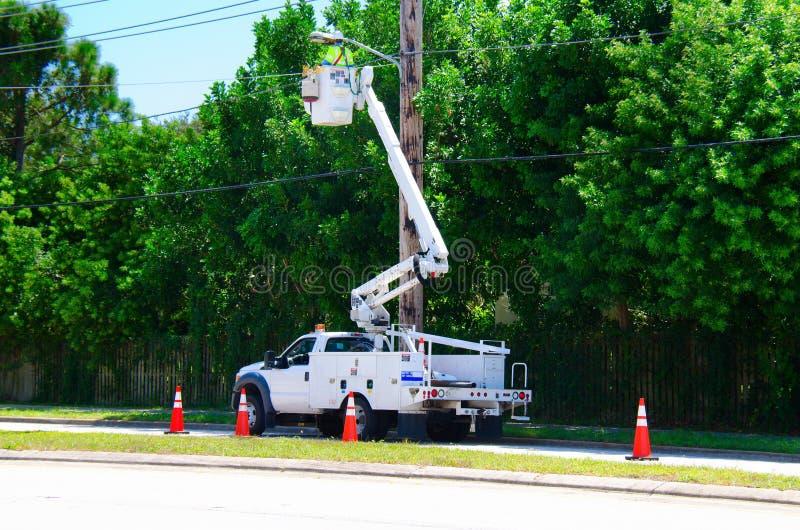 Electricista que trabaja en líneas de poder más elevado en una elevación foto de archivo
