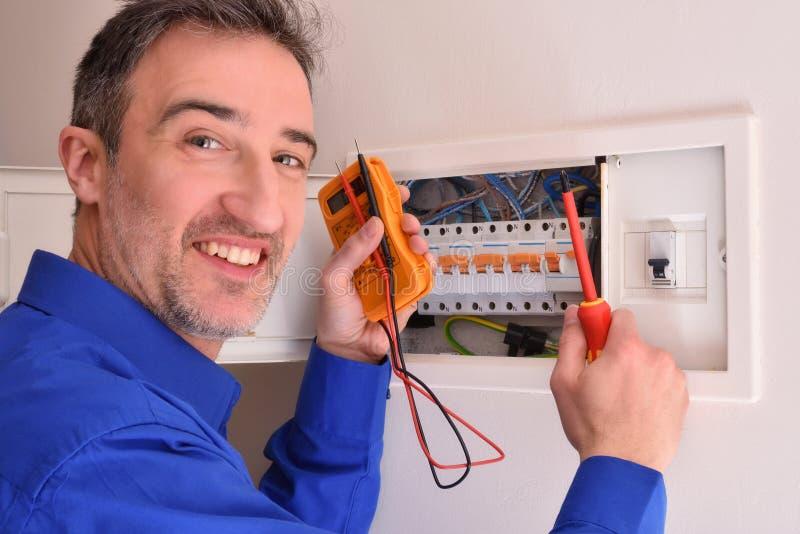 Electricista sonriente que hace reparaciones en caja de vivienda eléctrica fotos de archivo