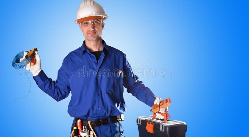 Electricista uniformado con las herramientas de las protecciones y del trabajo de la seguridad foto de archivo libre de regalías
