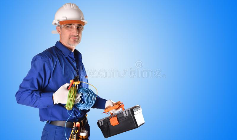 Electricista uniformado con protecciones de la seguridad y fondo de las herramientas del trabajo imágenes de archivo libres de regalías