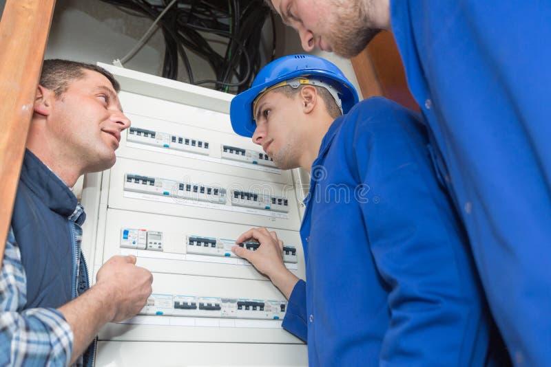 Electricistas del aprendiz que aprenden por el fusebox foto de archivo libre de regalías
