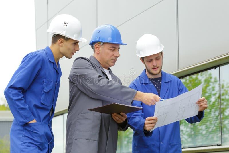 Electricistas del equipo en el emplazamiento de la obra fotografía de archivo
