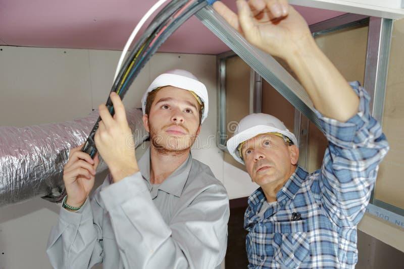 Electricistas del padre y del hijo que trabajan en techo de los edificios fotos de archivo