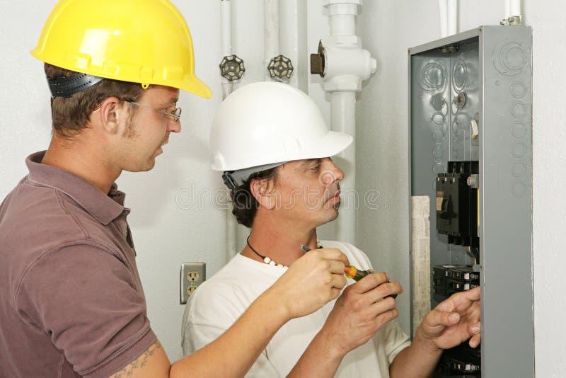 Electricistas que atan con alambre el panel foto de archivo