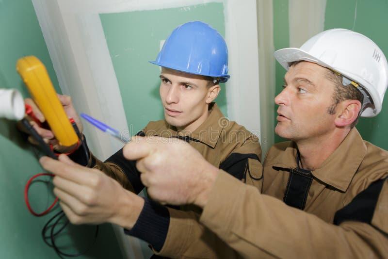 Electricistas que atan con alambre la nueva casa imagen de archivo
