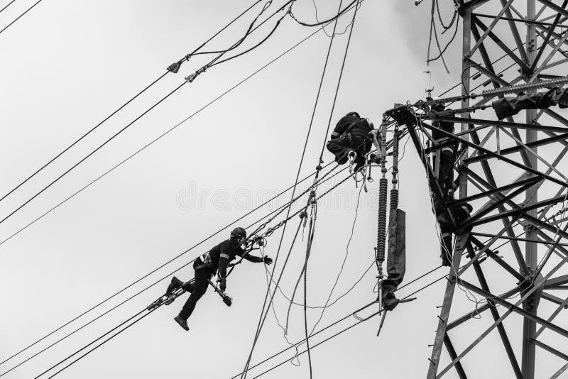 Electricistas que cuelgan blanco del negro de los cables de transmisión de la torre fotos de archivo libres de regalías