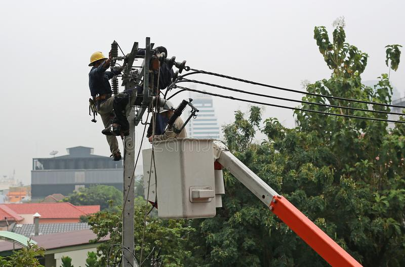 Electricistas que descansan mientras que trabaja para substituir el aislador eléctrico en el polo de la electricidad imagen de archivo