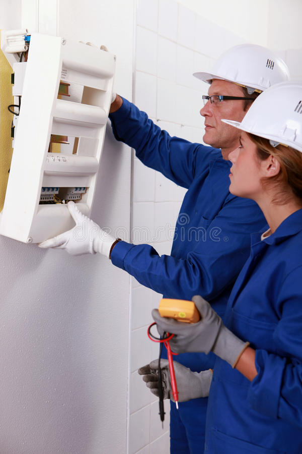 Electricistas que instalan un fusebox fotos de archivo libres de regalías