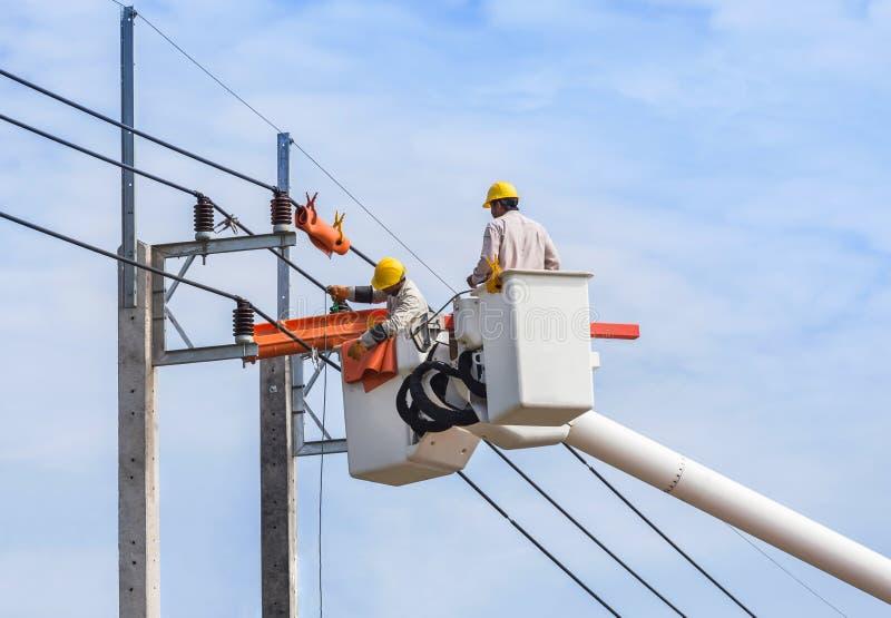 Electricistas que reparan el alambre de la línea eléctrica con la plataforma de elevación hidráulica del cubo fotos de archivo