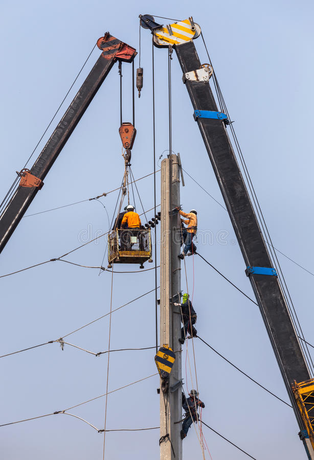 Electricistas que reparan el alambre en polo de poder de la electricidad con la plataforma hidráulica fotos de archivo