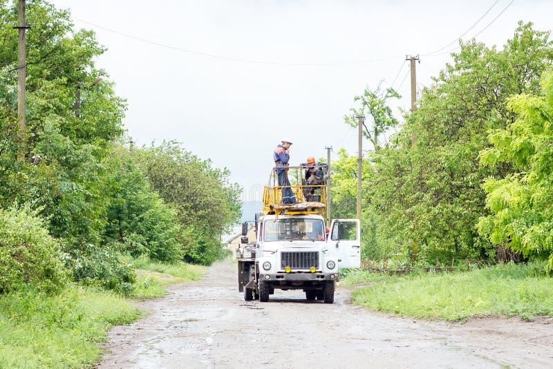 Electricistas que trabajan en los polos, a fotos de archivo