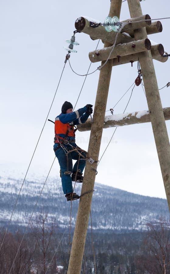 Electricistas que trabajan en un polo en invierno foto de archivo
