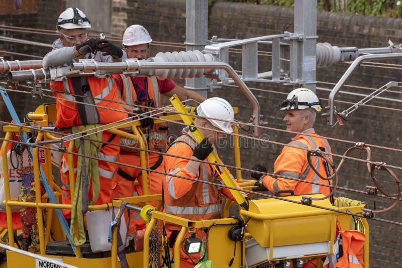 Electricistas que trabajan los cables de transmisión de arriba del ferrocarril imagen de archivo libre de regalías