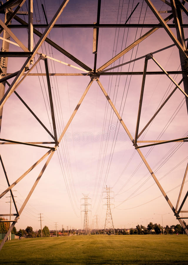 Electricity. Massive power lines stretch into the distance over a field royalty free stock photos