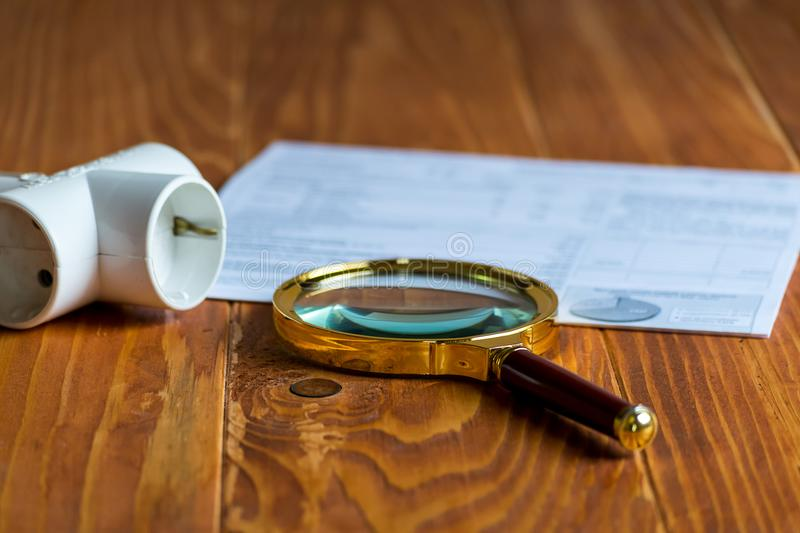 Electricity Bill on a table with magnifier and Electric Splitter stock photos