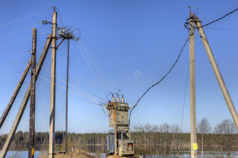 Electricity distribution transformer, electrical power substation in the countryside spring. stock image