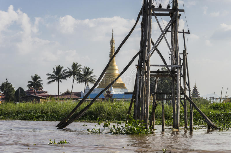 Electricity on Lake Inle. Pole with electricity and glod Pagoda in the background on Inle Lake in Myanmar Burma royalty free stock image