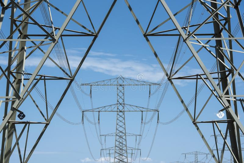 Electricity mast and transmission towers on the background on a blue sky stock image