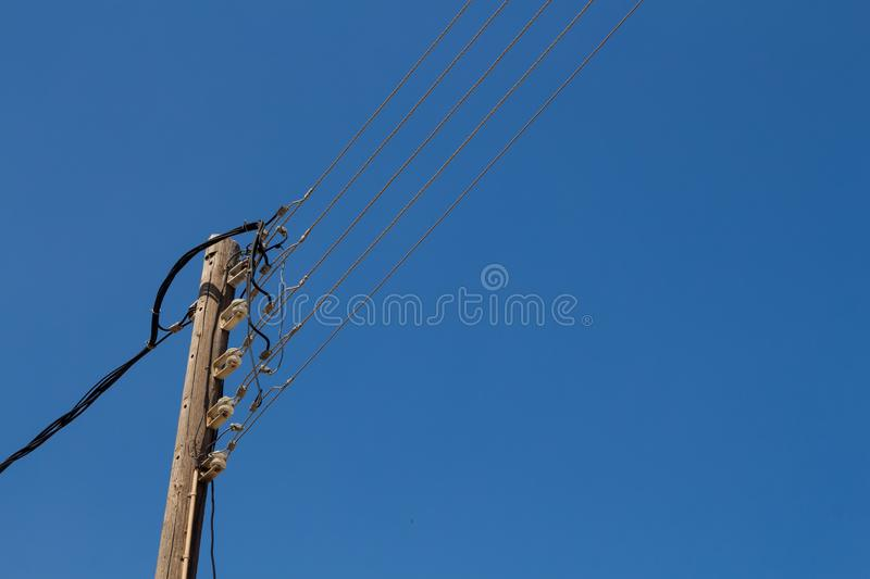 Electricity pole and cables, blue sky. Traditional woden pole for electricity cables. Mountain village Archanes, Crete, Greece royalty free stock photography