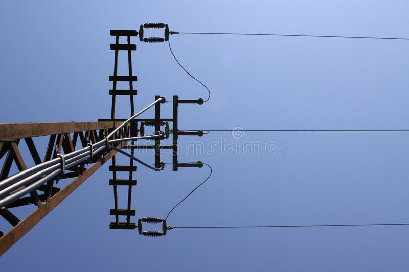 Electricity post. Frog perspective of a electricity post standing alone against a blue sky royalty free stock photos