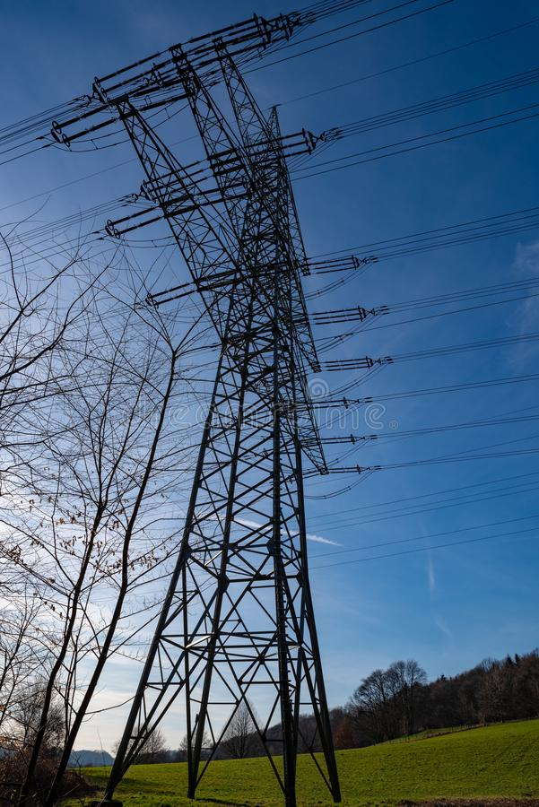 Electricity pylon against a blue sky in the evening sun, photographed from below stock photography