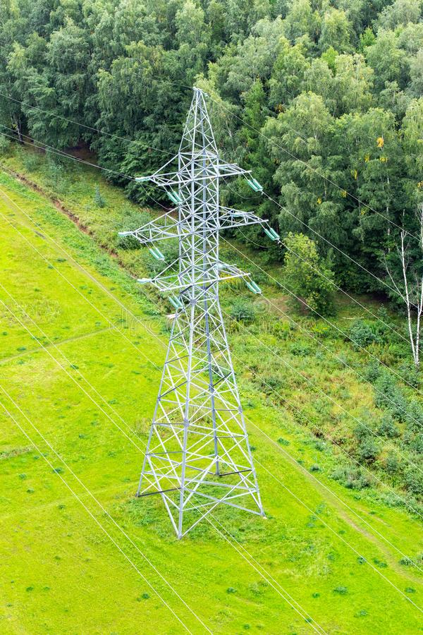 Electricity pylon on a green lawn in the background of the forest. High-voltage tower for power transmission, electrical wires royalty free stock photography