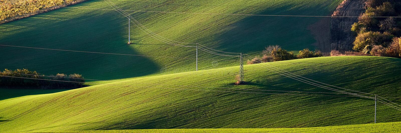 Electricity pylon and power lines on the green hills illuminated by the evening sun.South Moravian.Czech Republic. stock photo