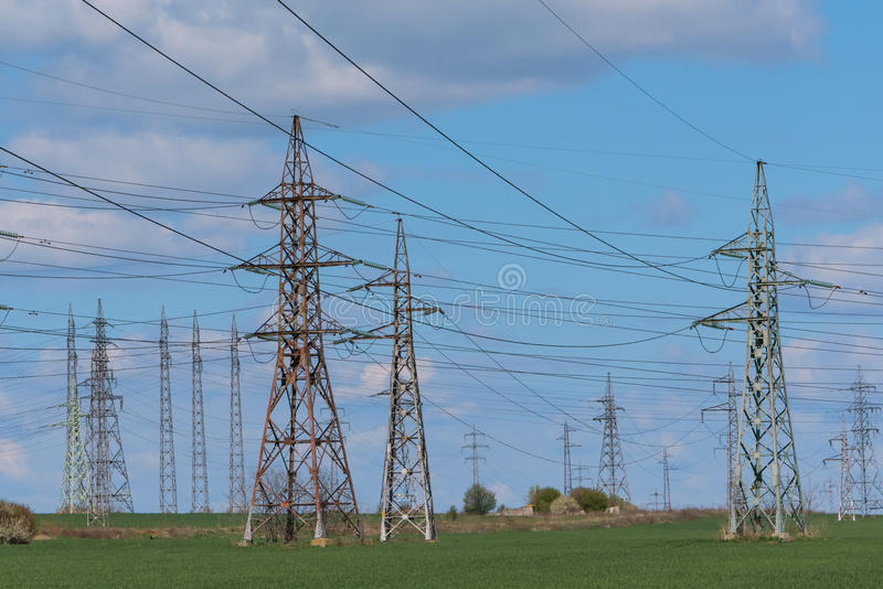 Electricity pylon silhouetted against blue sky sunshine background stock photography