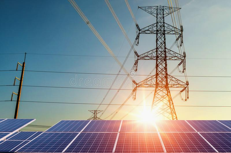electricity pylon with solar panels and sunset. Clean power energy concept royalty free stock photography