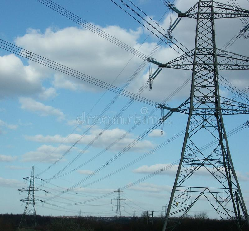 Electricity pylons. High voltage electricity pylons carrying cables recede into distance silhouetted against blue sky with white fluffy clouds royalty free stock photos