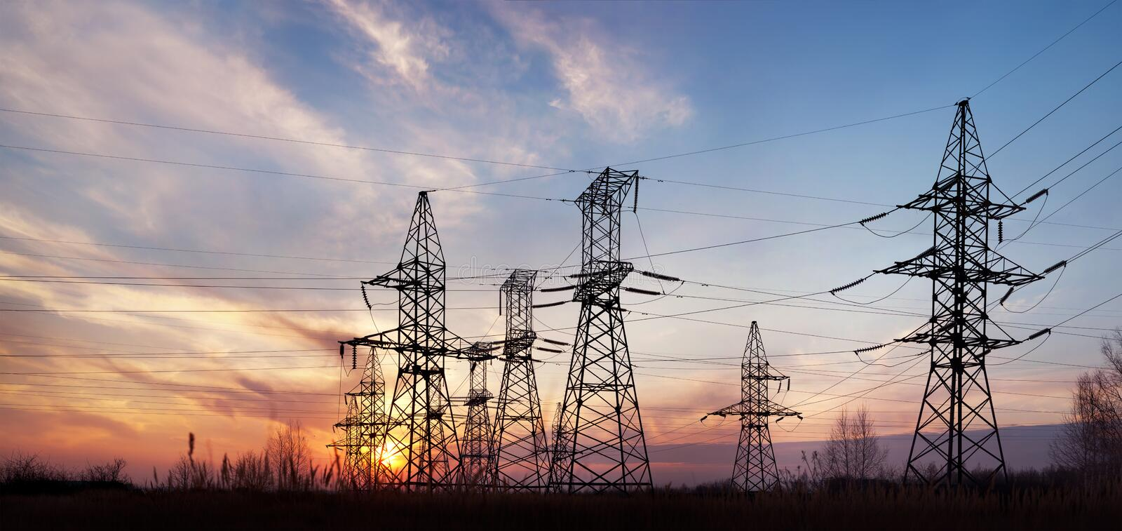 Electricity pylons and lines at dusk. royalty free stock images