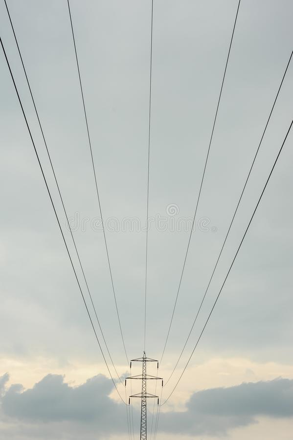 Electricity pylons and power lines. High voltage towers and cloudy sky. royalty free stock image