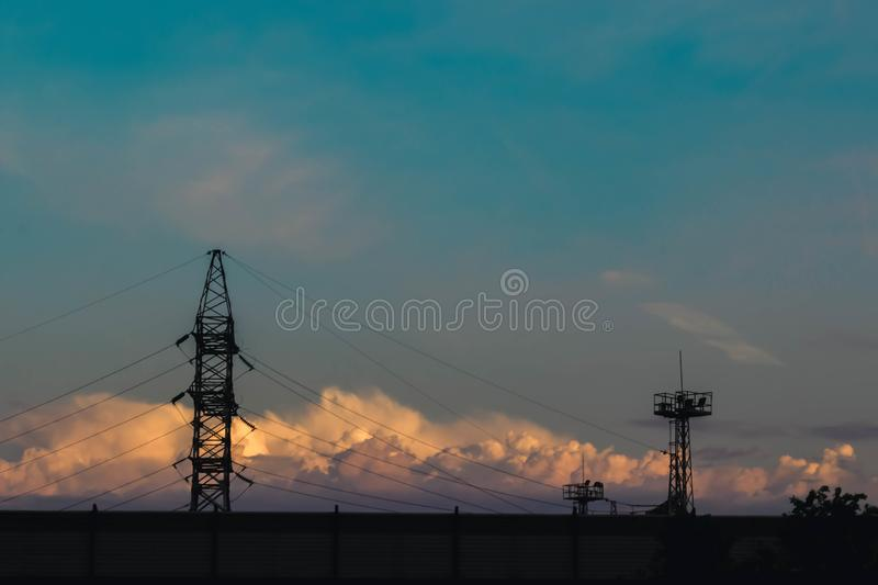 Electricity pylons, power lines silhouetted against a cloudy sky at sunset. royalty free stock image