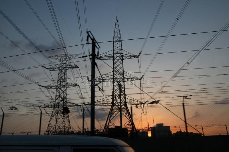Electricity pylons and power lines, at sunset stock photos
